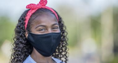 Smiling youth wearing mask outside